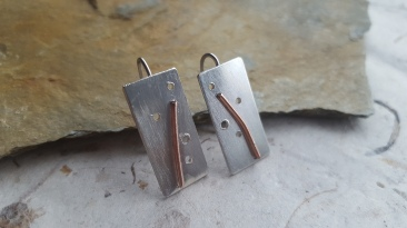 Modern solid silver earrings with hole detail and copper