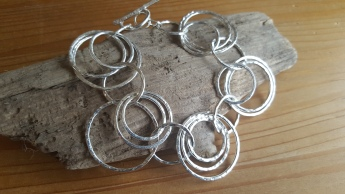 Heavy bracelet of Sterling Silver loops 3 different sizes. Hallmarked tag applied