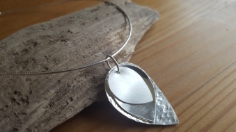 """3 layers of petals hang on a Sterling Silver Omega chain 16"""" long. The large petal hammered, miuddle one shiny and top petal brushed finish. They swing and have movement. £128.00"""