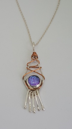 A real Boho style pendant with Prple Dichroic Glass, copper wrapped design and Sterling silver tassels, hangs on a silver chain